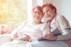 Caregiver and senior woman laughing. Young caregiver and senior women laughing together while sitting on sofa stock photos