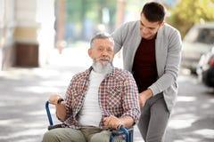 Young caregiver walking with senior man. Outdoors stock photos