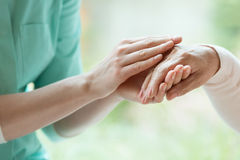 Caretaker massaging pensioner`s hand. Young caretaker massaging pensioner`s hand with Parkinson`s disease Stock Image