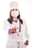 Young caring doctor in white uniform. A cute young doctoror health care worker in white uniform, protective mask, holding injection on white background Royalty Free Stock Images