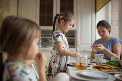 Young caring mother and her two little daughters eating pancakes with honey at the breakfast in the cozy kitchen stock photo