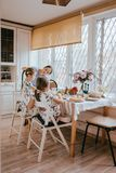 Young caring mother and her two little daughters have a breakfast in the light kitchen with large window stock photos