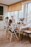 Young caring mother and her two little daughters have a breakfast in the light kitchen with large window stock images