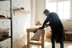 Young carpenter cutting wooden board with hand saw in workshop. Skilled carpenter with handsaw cutting wooden plank in workshop interior. Young craftsman holding Royalty Free Stock Photos