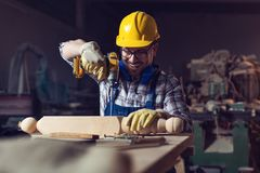 Carpenter drills a hole with an electrical drill. Young carpenter drills a hole with an electrical drill royalty free stock image