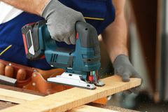 Young carpenter with electric fretsaw in workshop. Closeup Stock Image