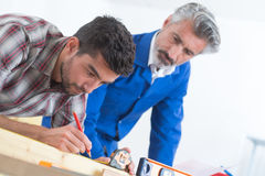 Young carpenter and father measuring wood in workshop royalty free stock image
