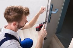 Young Carpenter Install Door Lock. With Wireless Screwdriver royalty free stock photo