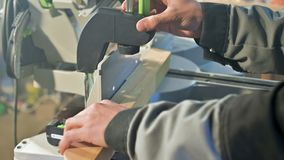 A young carpenter installs a wooden workpiece in a circular sawing machine. Home workshop. Novice businessman.  stock footage