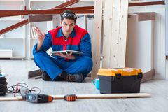 Young carpenter with notebook writing planning at construction r