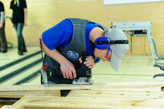 Young carpenter performs task of competition Stock Images