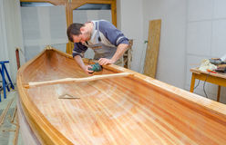 Young carpenter sanding new canoe in workshop. Young carpenter sanding new canoe of his own design Royalty Free Stock Photos