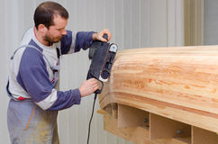 Young carpenter sanding new canoe in workshop Royalty Free Stock Image