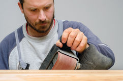 Young carpenter sanding new canoe in workshop Stock Photo