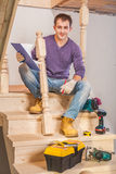 Young carpenter sitting on step of of ladder with tools Royalty Free Stock Image
