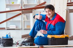 The young carpenter taking break from working with wooden planks. Young carpenter taking break from working with wooden planks Royalty Free Stock Photo