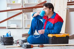 The young carpenter taking break from working with wooden planks. Young carpenter taking break from working with wooden planks Stock Image