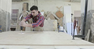 A young carpenter turning the self-tapping screw with a screwdriver at a furniture production. 4K A young carpenter turning the self-tapping screw with a stock video footage