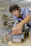 Young carpenter using belt sander Royalty Free Stock Images