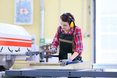 Young carpenter using sawing machine Royalty Free Stock Photography