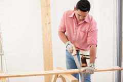 Young carpenter at work. Young Hispanic man doing some carpentry work at a houes Royalty Free Stock Images