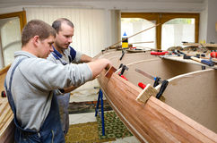 Young carpenters assembling new canoe of their design. Young carpenters assembling new canoe of their own design Stock Photos