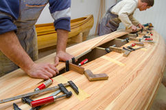 Young carpenters assembling new canoe Royalty Free Stock Image