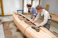 Young carpenters assembling new canoe of their own design Royalty Free Stock Image