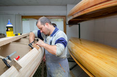 Young carpenters assembling new canoe of their own design Royalty Free Stock Images