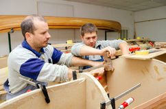 Young carpenters assembling new canoe of their own design.  Royalty Free Stock Photography
