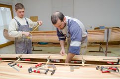 Young carpenters making, constructing, assembling wooden canoe Stock Image