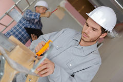 Young carpentry trainee sawing sawing plank Stock Photos