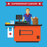Young cashier man standing in supermarket Royalty Free Stock Image
