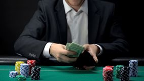 Young casino player taking all money out of wallet, making bet on poker game stock images