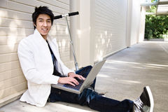 Young casual asian male with laptop Royalty Free Stock Images