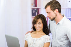 Young casual attractive couple using laptop Royalty Free Stock Photo