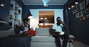 Young casual black couple sit separately on couch watching movies not talking after fighting and quarreling slow motion.