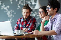 Young Casual Business People in Office. Side view of group of young creative people wearing casual clothes collaborating at meeting in office and smiling looking stock photo