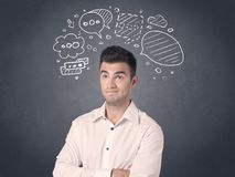 Businessman with speech bubbles. Young casual businessman with drawn speech bubbles over his head Royalty Free Stock Photo
