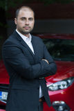 Young casual businessman with red car Stock Photos