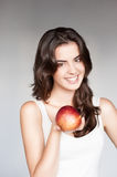 Young casual caucasian girl with red apple. Portrait young attractive cheerful casual caucasian girl with red apple royalty free stock photography