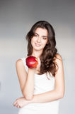 Young casual caucasian girl with red apple. Portrait young attractive cheerful casual caucasian girl with red apple on gray background royalty free stock photo