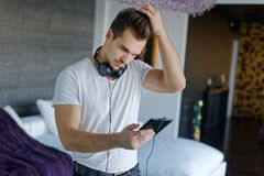 Young casual caucasian man worry by message on tablet Stock Photos