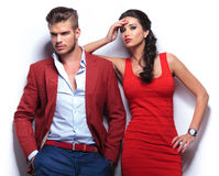 Young casual couple against white wall. Men looking away and women looking at the camera stock photography