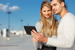 Young casual couple browsing internet by tablet outdoor Royalty Free Stock Photos