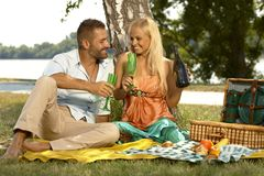 Young casual couple drinking champagne at picnic. Young happy caucasian casual couple drinking champagne sitting at picnic. Handsome men and attractive women Royalty Free Stock Photo