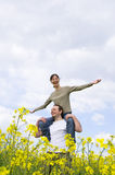 Young casual couple enjoying summer. Field with a lot of copy space Stock Photography