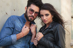 Young casual couple with hands on jackets. Young casual couple holding their hands on their jackets and looking into the camera Stock Photo