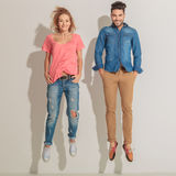 Young casual couple jumping. While holding theri hands in pockets Royalty Free Stock Photography