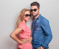 Young casual couple posing, both wearing sunglasses. Side view of a young casual couple posing, both wearing sunglasses Royalty Free Stock Photos